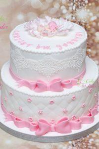 tort na chrzest swiety – komunia swieta – minsk mazowiecki –  recznie wykonane ozdoby – figurka niemowle – dziecko w kwiatku – platki kwiatu – jadalna koronka – wstazki z kokardami – pikowany tort – tort pietrowy – ozdobny napis – chrzest swiety – bialo rozowy – tort dla dziewczynki
